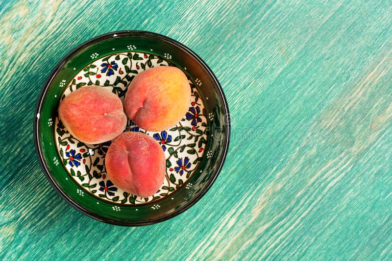 Ripe peaches in a dish on a light rustic background. royalty free stock photos