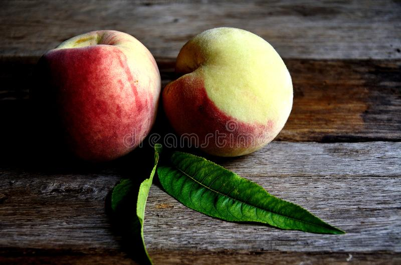 Two ripe peaches with leaves lie on old wooden boards. Ripe peaches on the kitchen table for cooking. Two ripe peaches with leaves lie on old wooden boards. Two royalty free stock images
