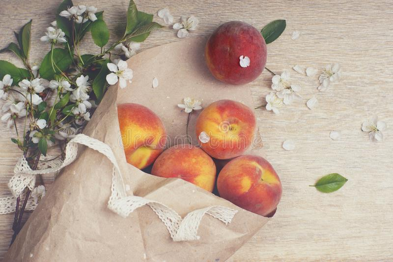 Ripe peaches are poured out of a package made from craft paper, next to a branch with white flowers, top view stock photos