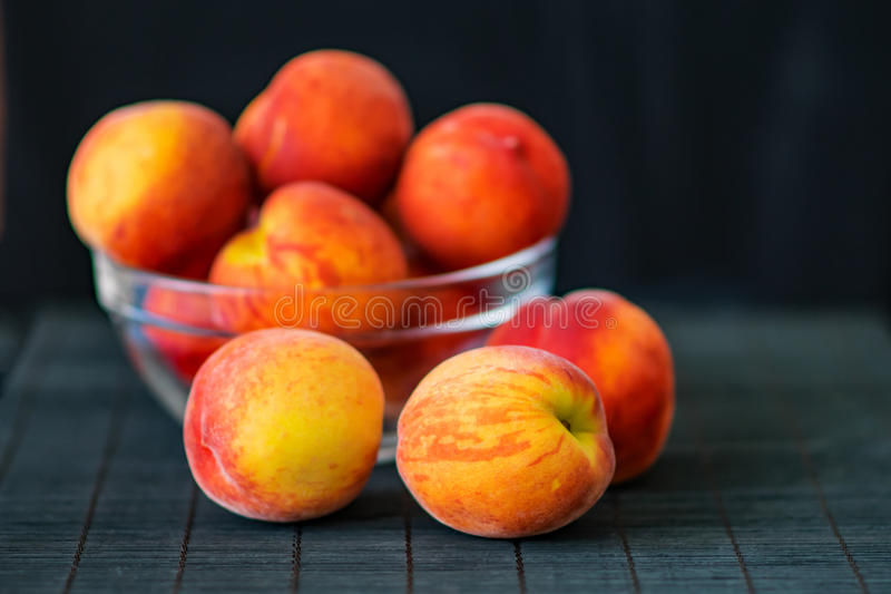 Ripe peaches in a transparent glass bowl on a black background. Summer fruits. Health Care Concept royalty free stock photos