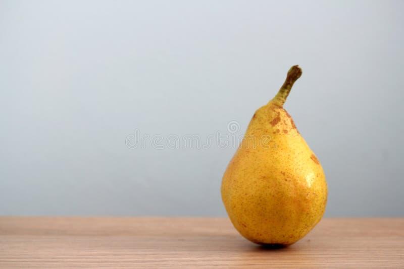 Ripe pear on desk stock image