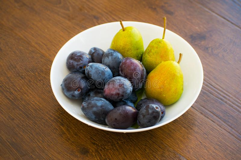 Pears and plums on a white plate. Ripe pear and plums lie on a white plate. Summer food with fresh fruits in a plate. stock photo