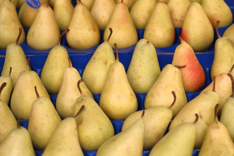 Ripe pears in a box. With cells on the market counter royalty free stock image