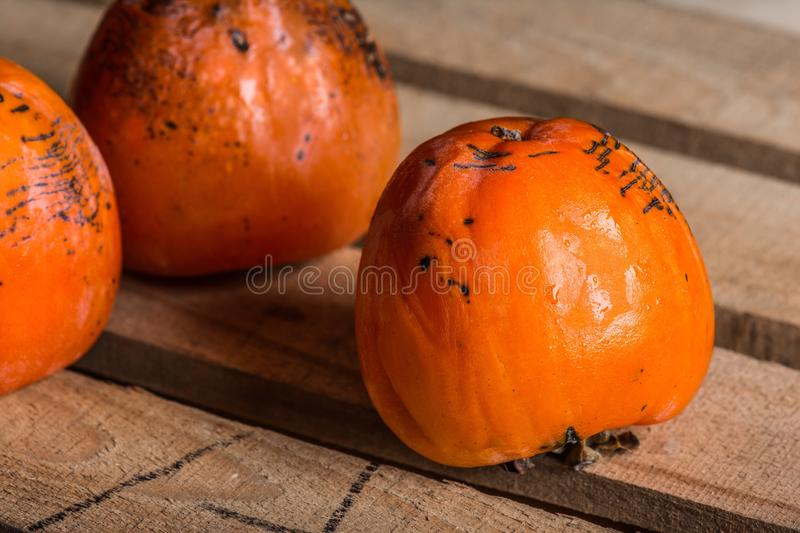 Ripe persimmon of a winter crop. The frozen persimmon of a winter crop stock photo