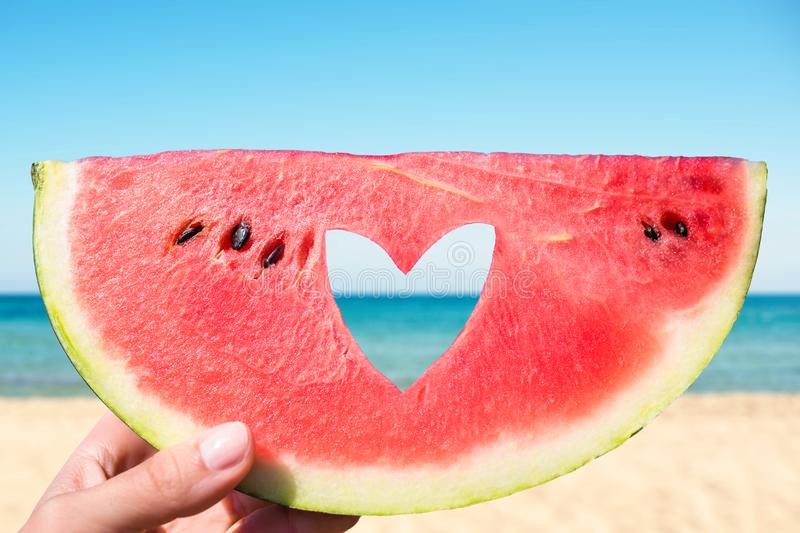 Ripe piece of watermelon with heart shape hole in female hands on the background of the beach on a hot summer day. stock photo