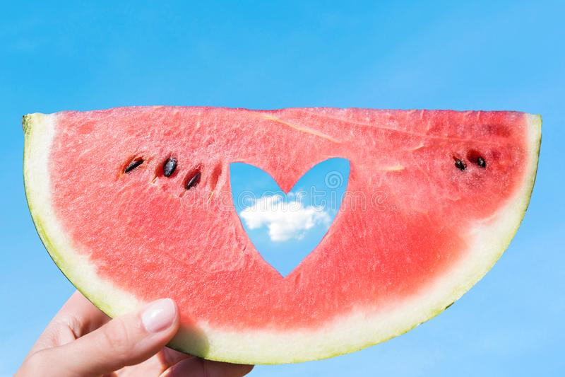 Ripe piece of watermelon with heart shape hole in female hands on the background of the blue sky with little cloud on a hot summer. Day. Concept stock image