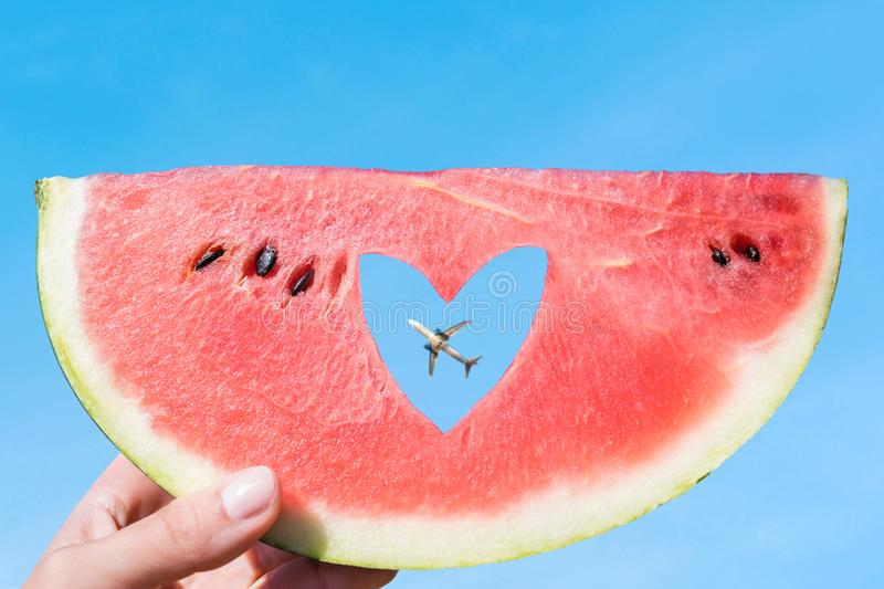 Ripe piece of watermelon with heart shape hole in female hands on the background of the blue sky and plane. Summer Concept. Ripe piece of watermelon with heart stock photography