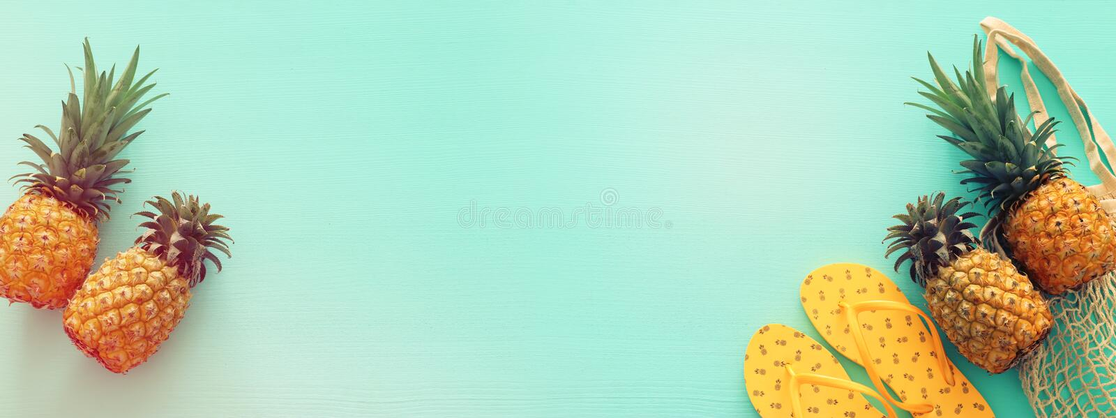 Ripe pineapple and beach sea life style objects over pastel mint blue wooden background. Tropical summer vacation concept. banner stock images