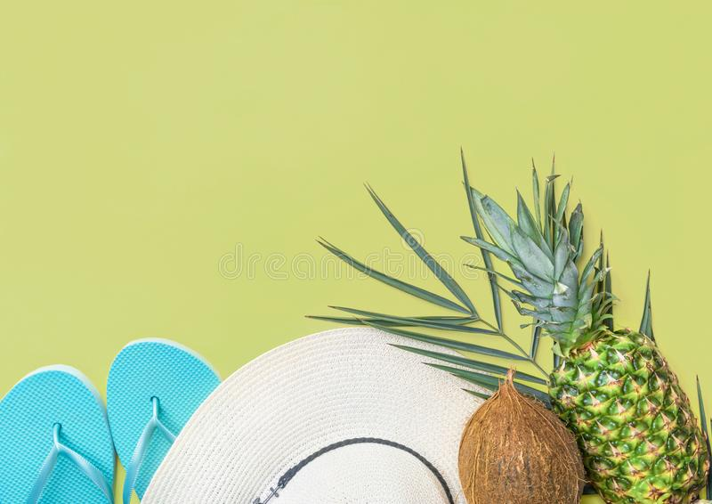Ripe pineapple coconut on green palm leaf white straw hat blue slippers on pastel chartreuse background. Summer vacation fun stock photo