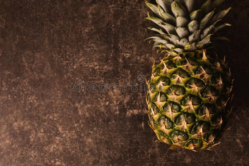 Ripe pineapple lying on a dark marble table. Delicious fruit. royalty free stock images
