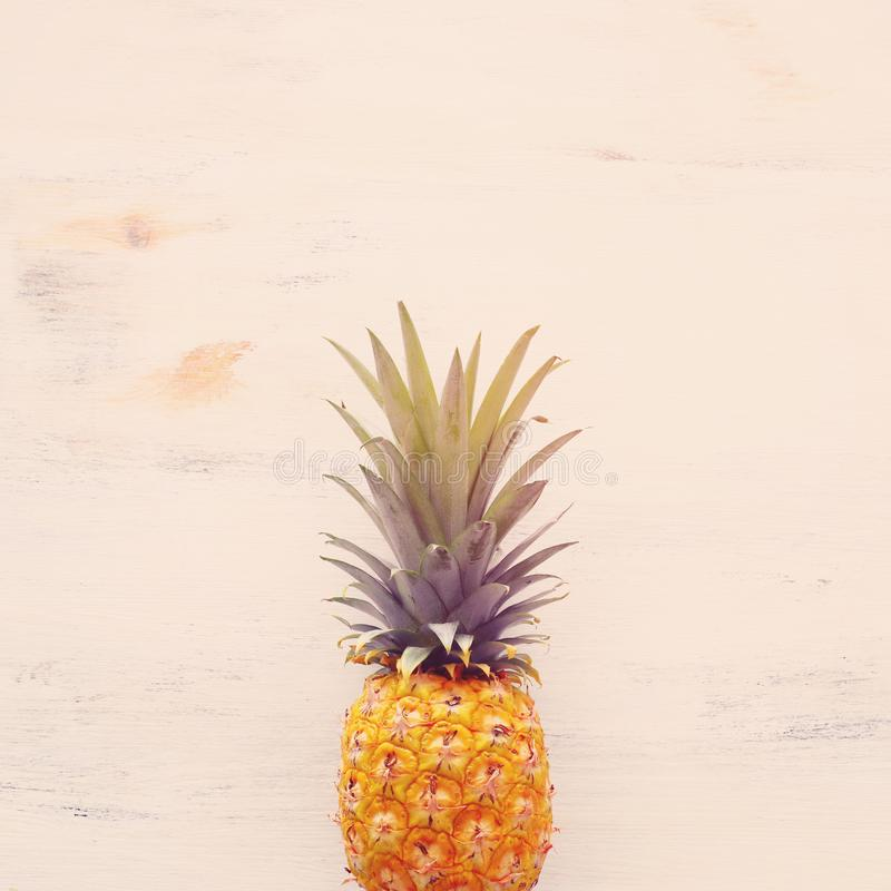 Ripe pineapple over white wooden background. Beach and tropical theme. Top view royalty free stock photos