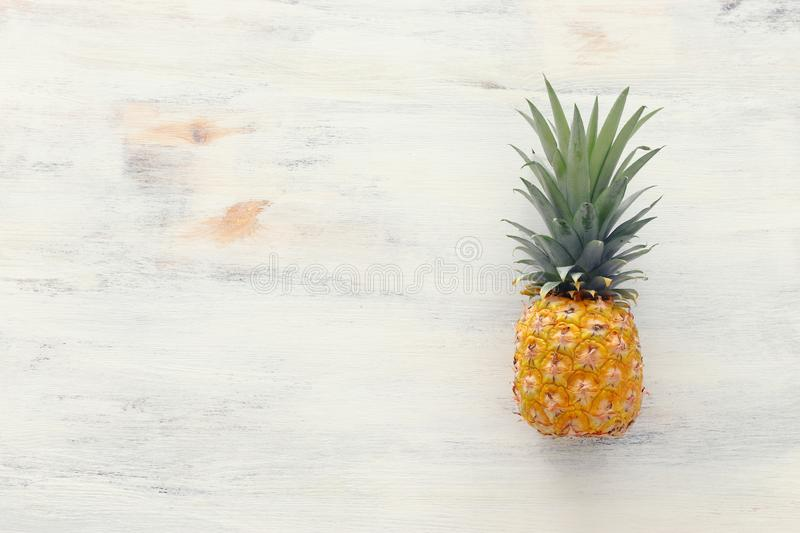 Ripe pineapple over white wooden background. Beach and tropical theme. Top view royalty free stock photography