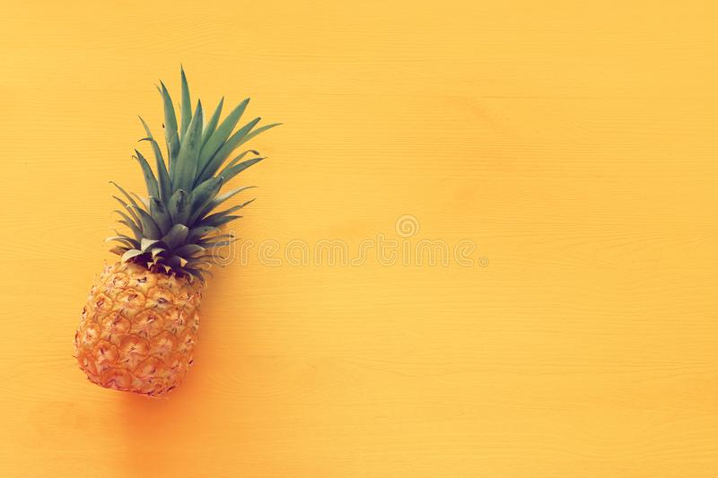 Ripe pineapple over yellow wooden background. Beach and tropical theme. Top view.  stock image