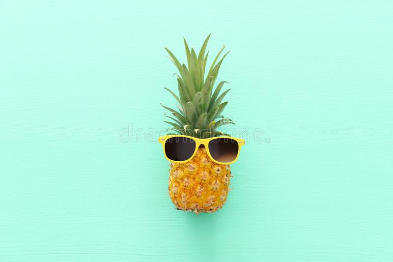 Ripe pineapple in stylish sunglasses over wooden blue background. Tropical summer vacation concept. top vew.  stock photography