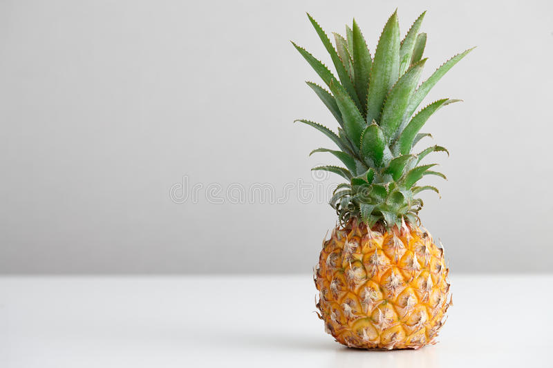 Ripe pineapple on a white table royalty free stock photography