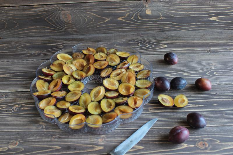 Ripe plums lay on table, harvesting and drying of fruits. royalty free stock photo