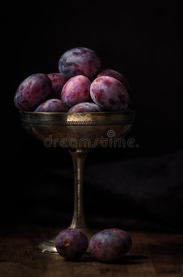 Ripe plums in a old silver cup in dark food photography style. Ripe plums in a old silver cup in a dark food photography style stock photography