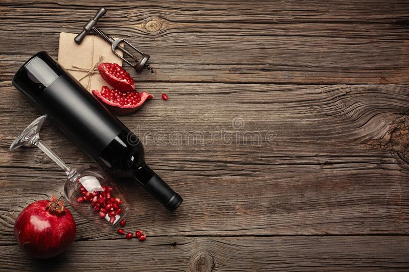 Ripe pomegranate fruit with a glass of wine, a bottle and a corkscrew on a wooden background stock photos
