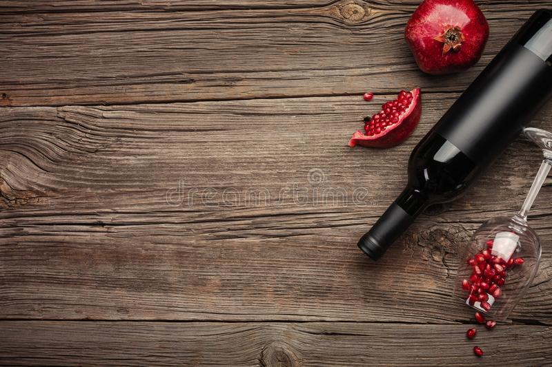 Ripe pomegranate fruit with a glass of wine, a bottle and a corkscrew on a wooden background royalty free stock photography