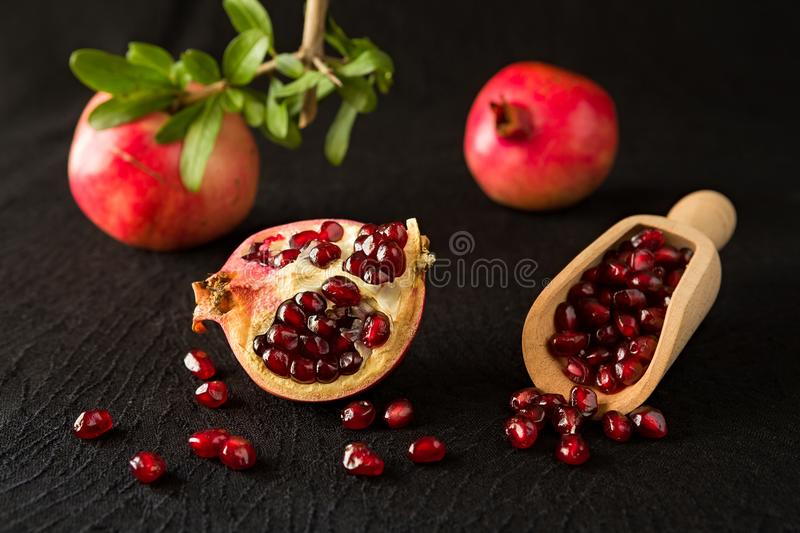 Ripe pomegranate fruits and bailer with seeds inside. Over a black textured background stock photography