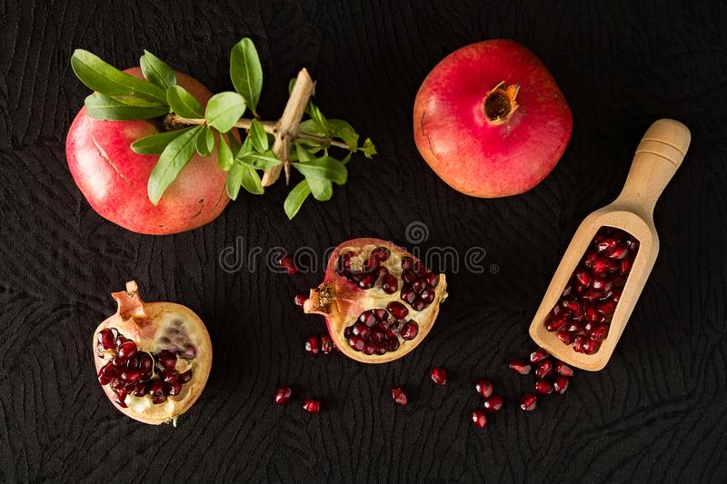 Ripe pomegranate fruits and bailer with seeds inside seen from a. Bove over a black textured background royalty free stock photography