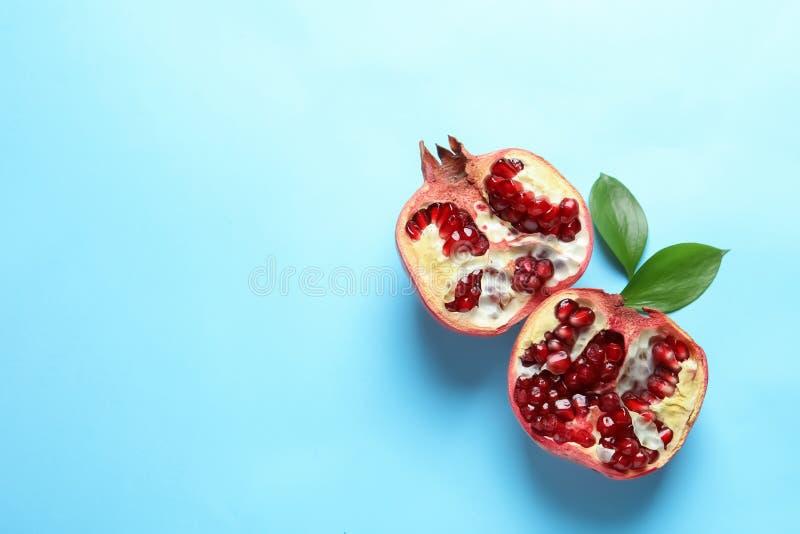 Ripe pomegranate halves on color background stock photography