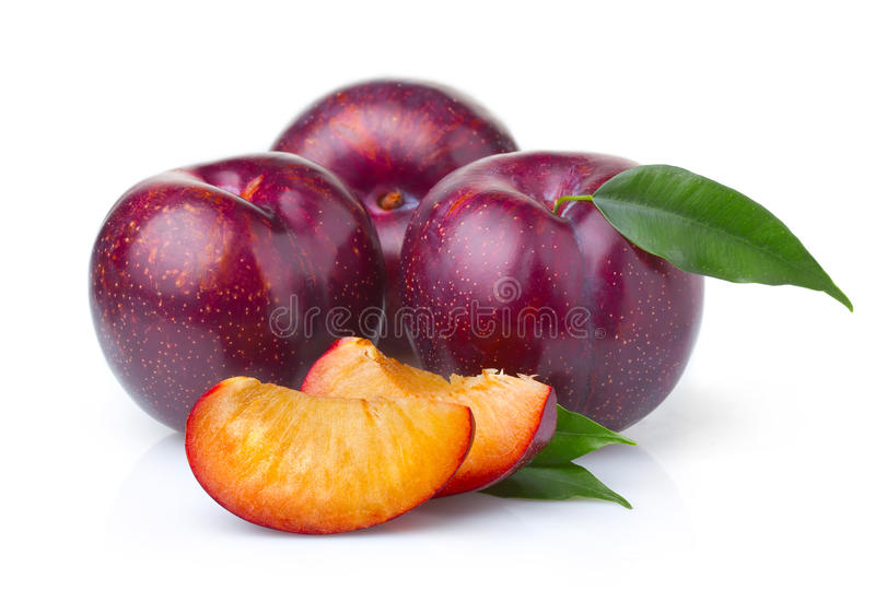 Ripe purple plum fruits with green leaves royalty free stock images