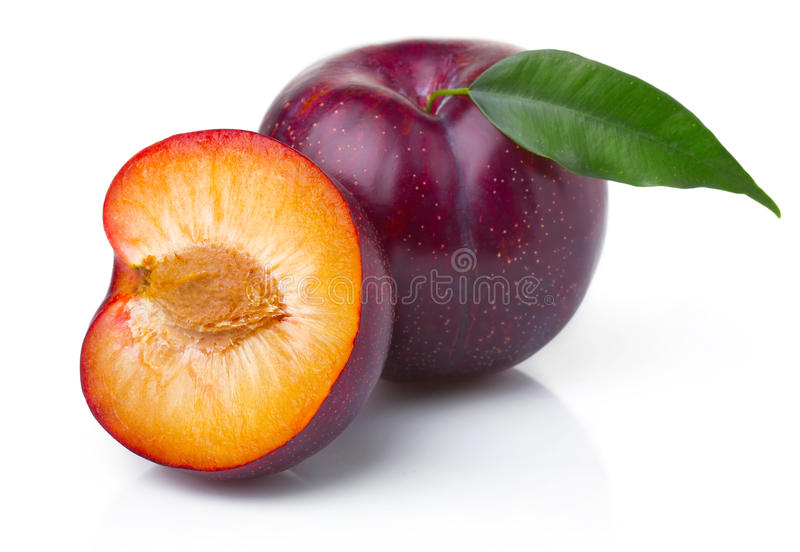 Ripe purple plum fruits with green leaves stock photography