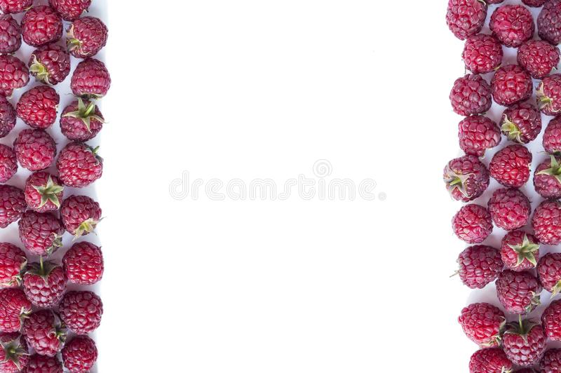Ripe raspberries on white background. Raspberries at border of image with copy space for text. Various fresh summer berries. royalty free stock images