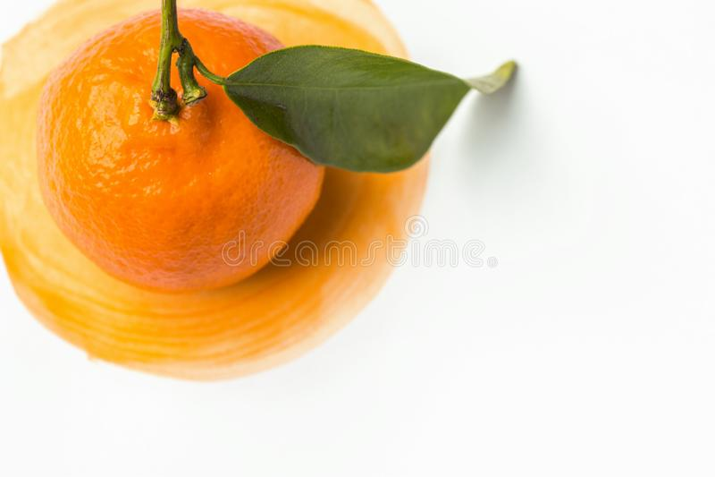 Ripe raw bright orange tangerine with stem green leaf on hand painted watercolor splashes paintbrush stroke background. On white paper. Summer fruits citrus royalty free stock photography