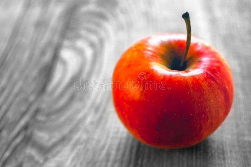 Ripe red apple on colorless rustic wooden background. Color pop effect stock photography