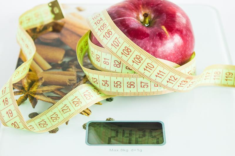 Ripe red Apple with roulette on the scales. Ripe red fresh Apple with green roulette on grocery scales on white background stock photos