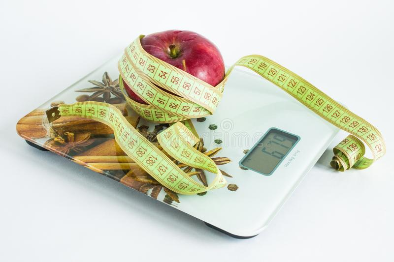 Ripe red Apple with roulette on the scales. Ripe red fresh Apple with green roulette on grocery scales on white background royalty free stock photo
