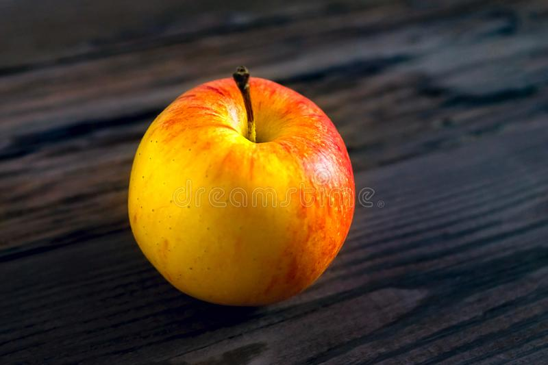 Ripe red apple on rustic dark wooden table royalty free stock photography