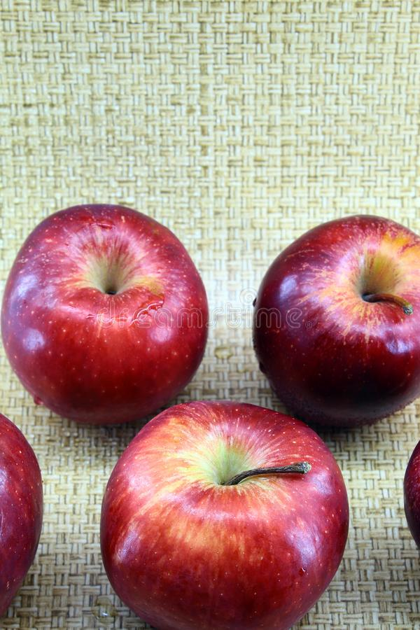 Ripe red apples medium size vertical photos. Vertical photo, light brown background, a little red ripe fresh fruit, apples with skin, whole, medium size. Healthy stock image