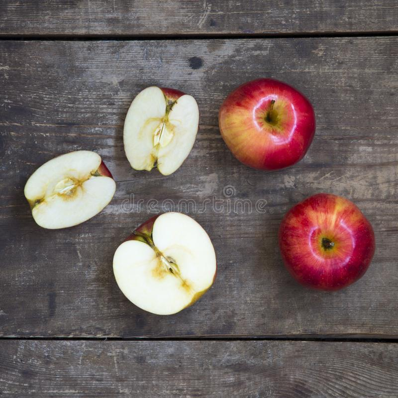 Ripe red apples and slices on dark wooden surface. From above. Top view stock photos