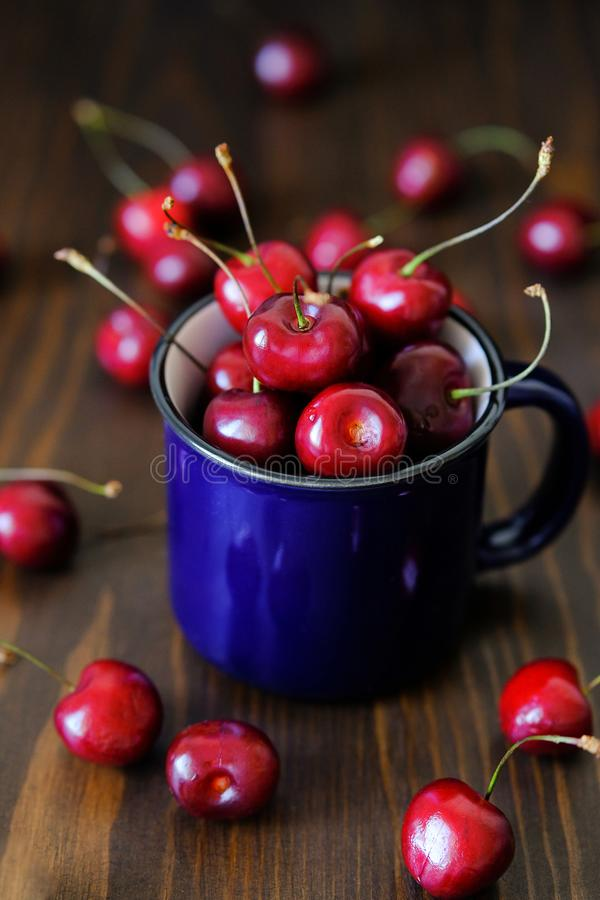 Ripe red cherries in a glass on a wooden background. Juicy berries and fruits for detox diet. Vegetarianism, veganism, raw food. stock images