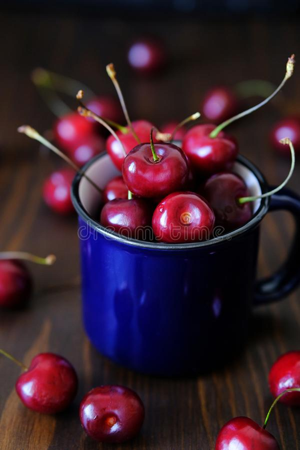 Ripe red cherries in a glass on a wooden background. Juicy berries and fruits for detox diet. Vegetarianism, veganism, raw food. royalty free stock photography