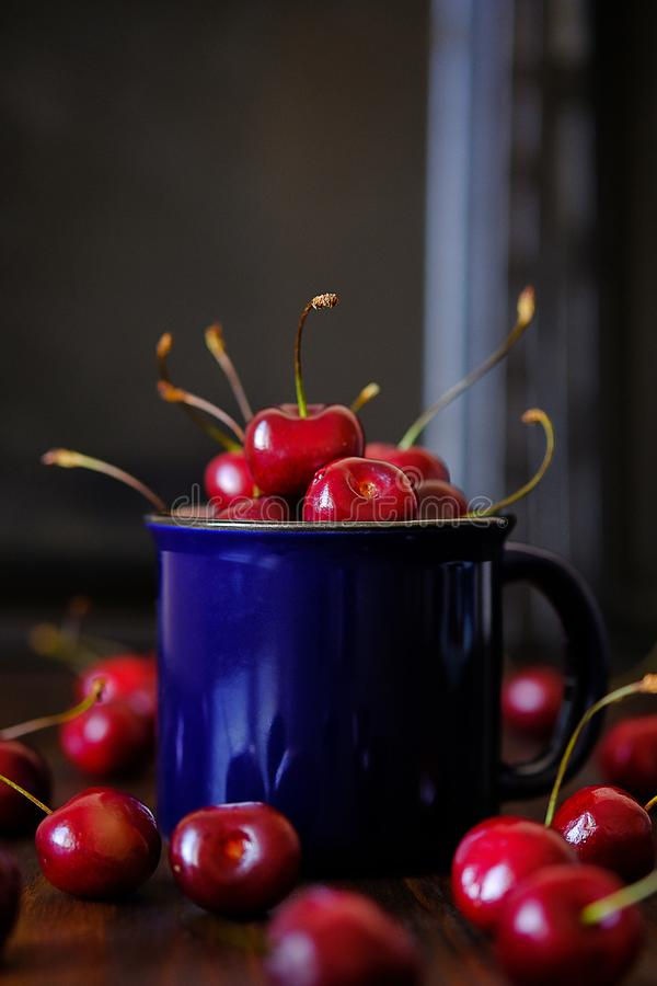 Ripe red cherries in a glass on a wooden background. Juicy berries and fruits for detox diet. Vegetarianism, veganism, raw food. royalty free stock image