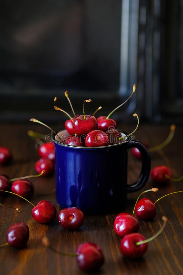 Ripe red cherries in a glass on a wooden background. Juicy berries and fruits for detox diet. Vegetarianism, veganism, raw food. stock photos