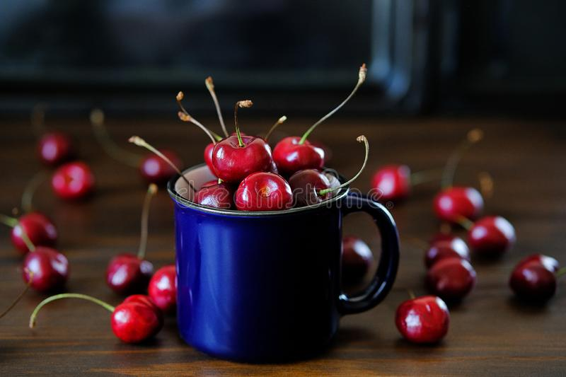 Ripe red cherries in a glass on a wooden background. Juicy berries and fruits for detox diet. Vegetarianism, veganism, raw food. royalty free stock images