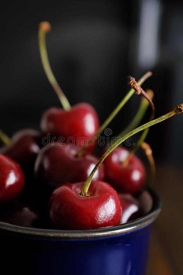 Ripe red cherries in a glass on a wooden background. Juicy berries and fruits. Vegetarianism, veganism, raw food diet. Proper royalty free stock photo