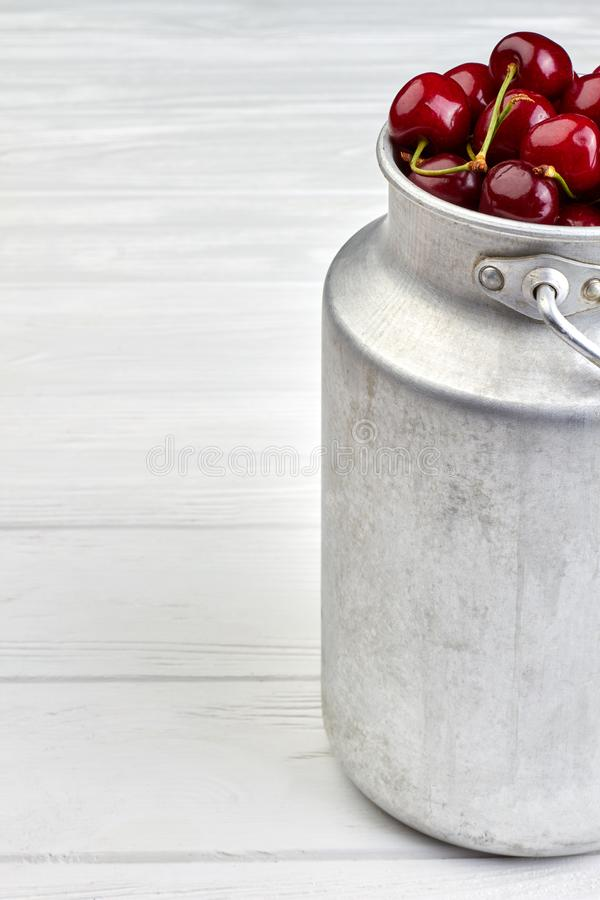 Ripe red cherries in vintage bucket, cropped image. Tasty summer berries in metal container, copy space stock image