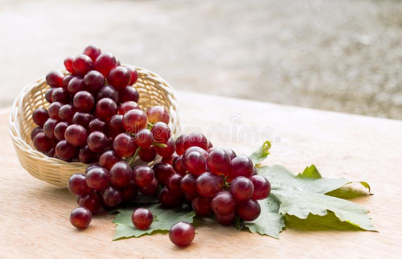 Ripe Red Grape with leaves which fruit fresh in basket on a wooden table background royalty free stock photography