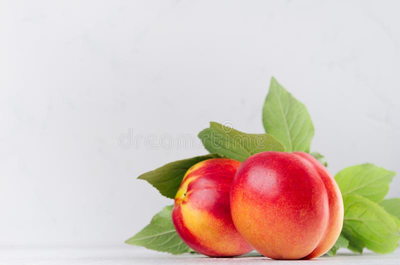 Ripe red nectarines with green leaves closeup on soft white wood board. Sweet summer fruits. stock photo