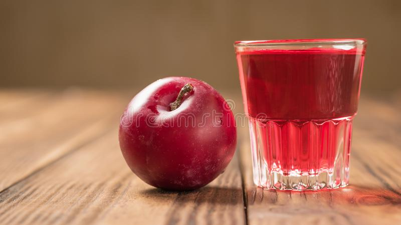 Ripe red plum and a glass of plum homemade liqueur on the table. Homemade alcoholic drink made from berries plum stock photography