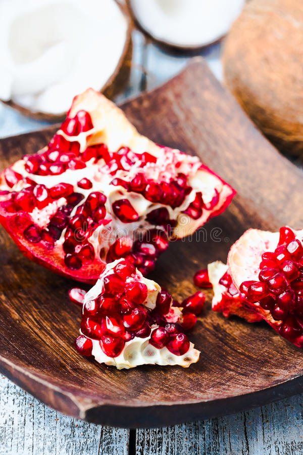Ripe red pomegranate in a wooden bowl,blue background stock photos