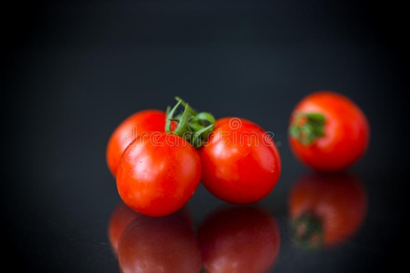 Ripe red small cherry tomatoes on a black stock photography