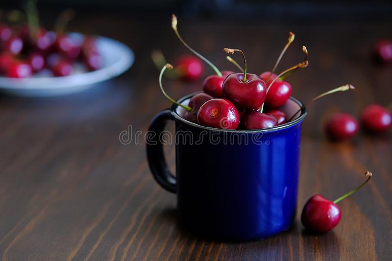 Ripe red sweet cherry in a glass on a wooden background. Juicy berries and fruits. Vegetarianism, veganism, raw food diet. Proper royalty free stock photo