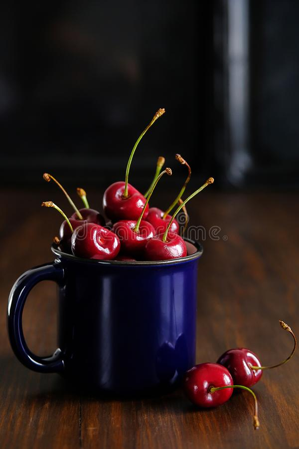Ripe red sweet cherry in a glass on a wooden background. Juicy berries and fruits. Vegetarianism, veganism, raw food diet. Proper royalty free stock photography